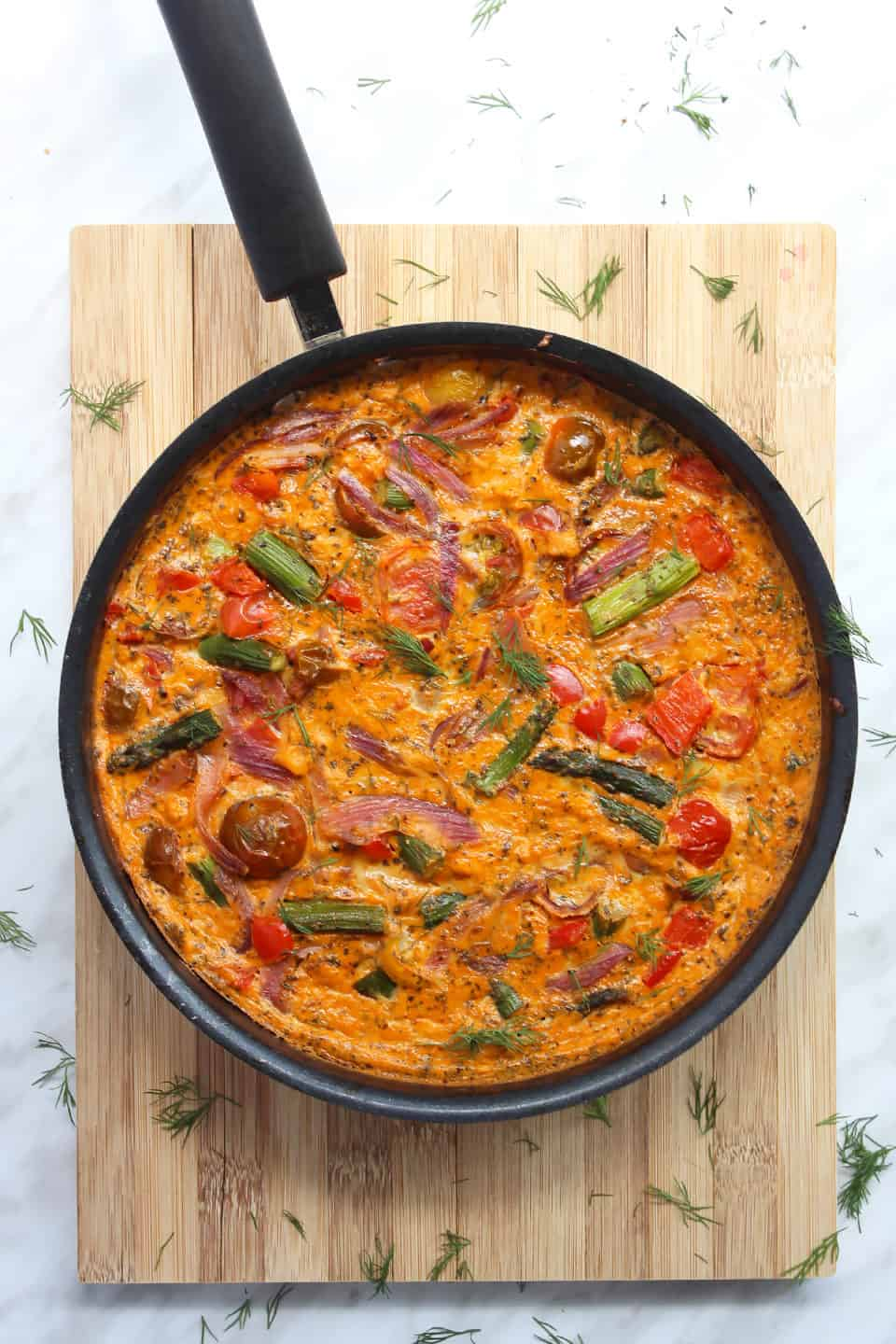 A oven baked frittata in a skillet on a wooden chopping board