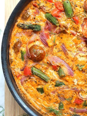 A baked red pesto frittata in a frying pan