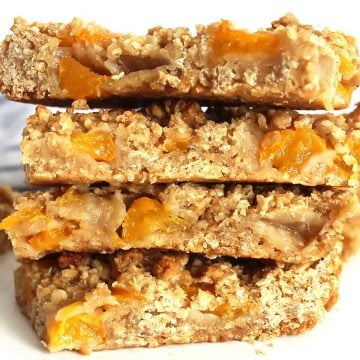 Close up of four peach oatmeal bars stacked on top of each other