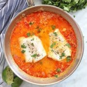 Poached cod in a pan with coconut milk and spices