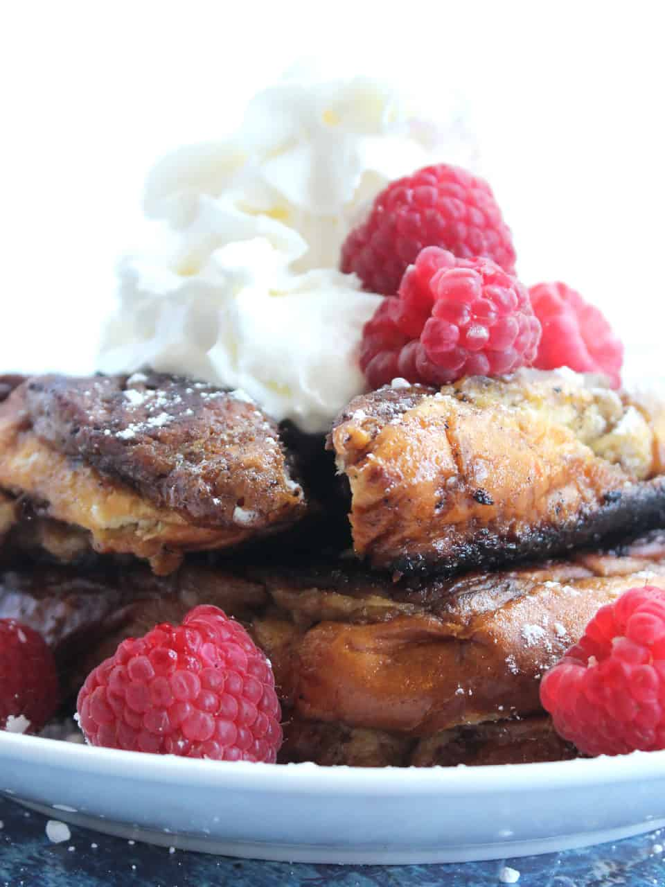 Chocolate French toast topped with whipped cream.