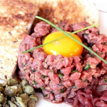 Steak tartare served with toast and topped with an egg yolk