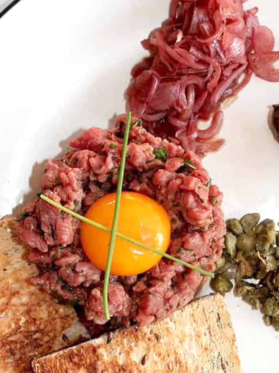 Overhead shot of an egg yolk placed on top of the steak tartare and garnished with chives