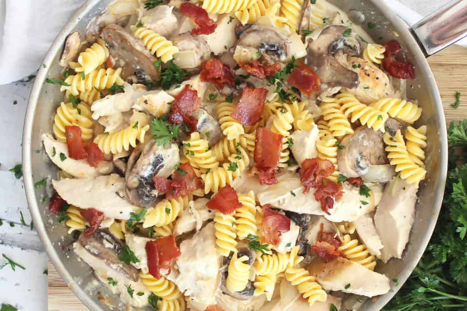 Chicken and mushroom pasta in a skillet topped with bacon bits.
