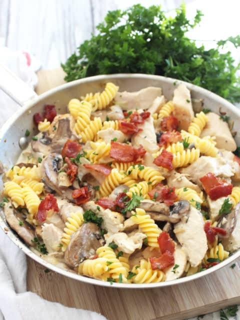 Chicken and mushroom pasta topped with bacon pieces in a silver skillet.