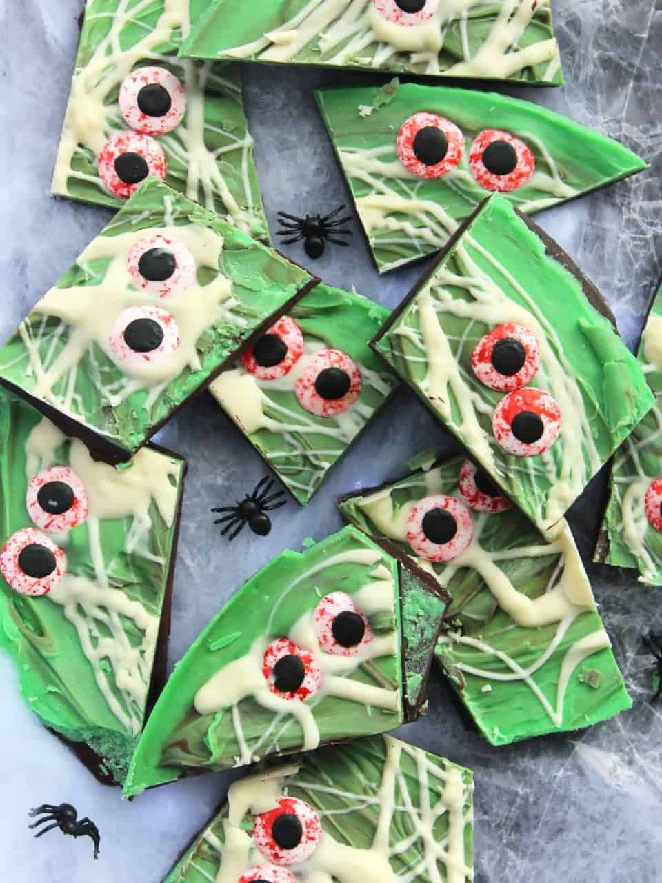 Nine pieces of Halloween bark with plastic spiders around them.