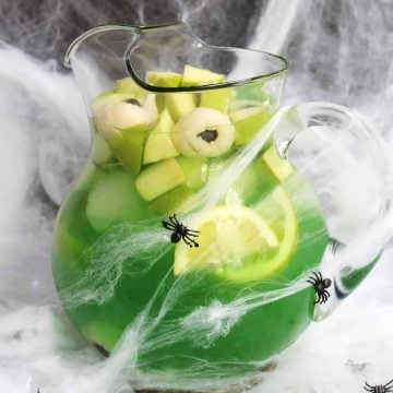 A jug of green sangria with cobwebs around it.