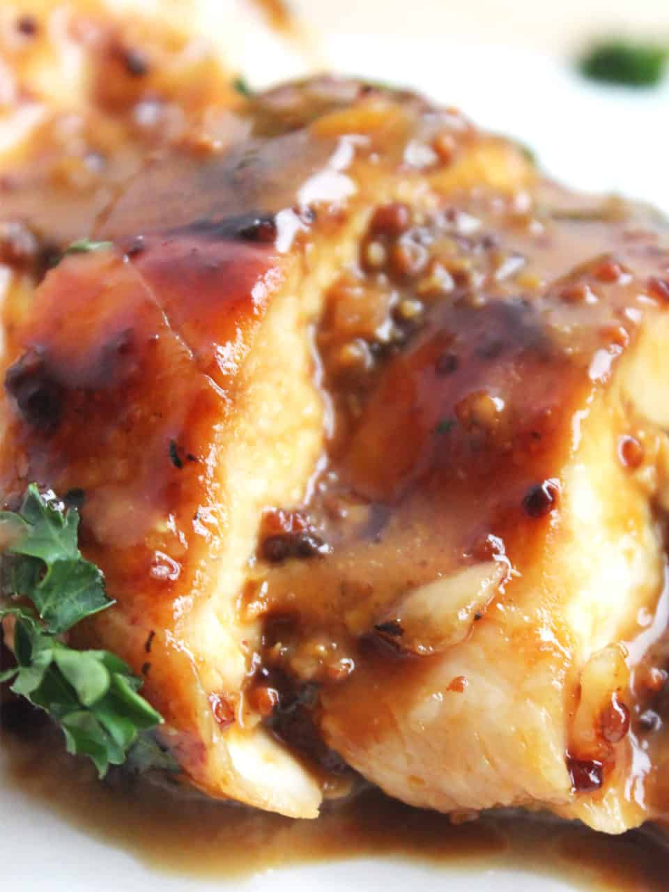 Close up of a sliced chicken breast finished with honey and mustard sauce.