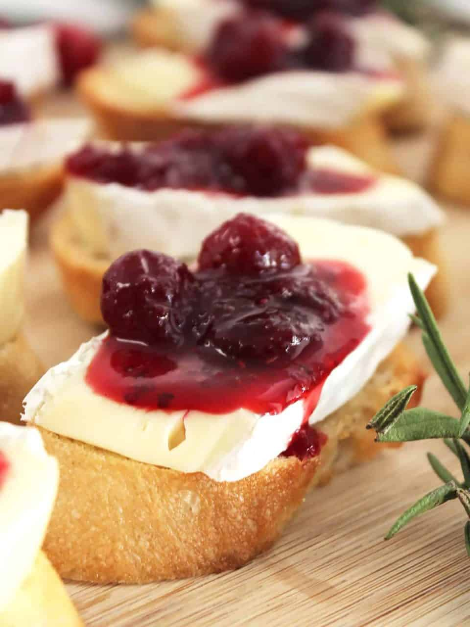 A crostini topped with brie and cranberry sauce.