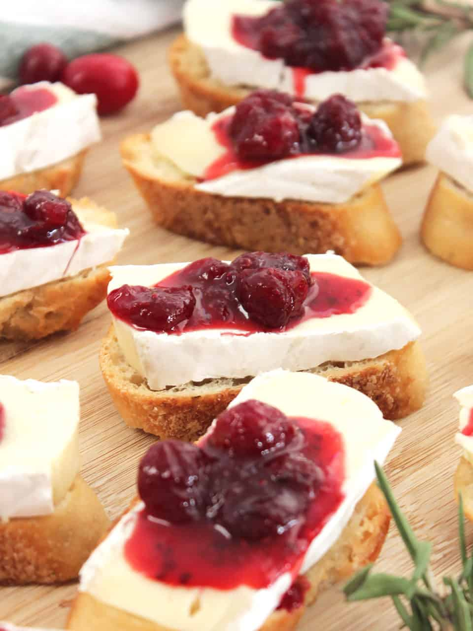 Four crostini topped with brie and cranberry sauce with sprigs of thyme.