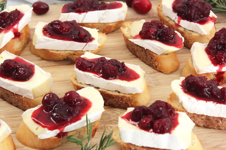 Eleven brie and cranberry crostini on a wooden chopping board.
