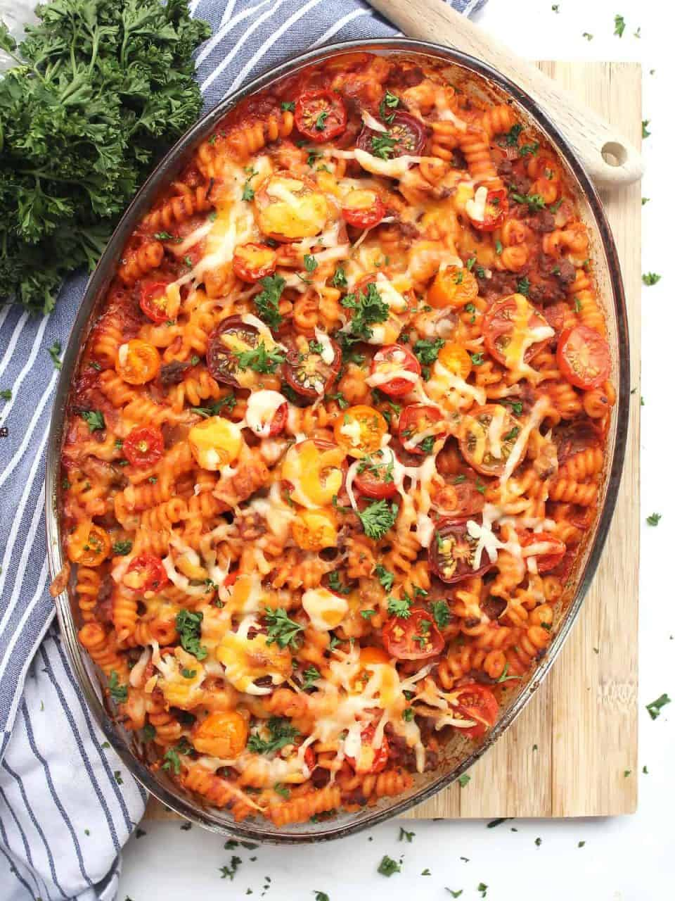 Baked ground beef pasta bake in a glass dish on a wooden chopping board.