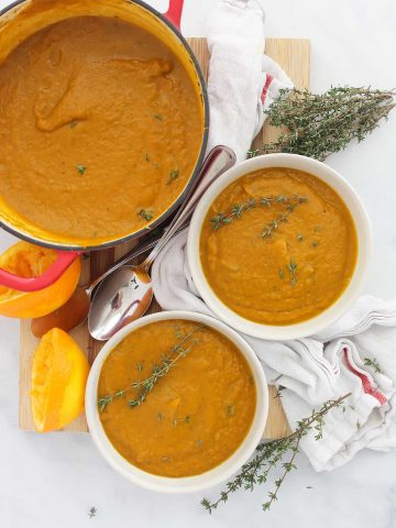 Carrot orange soup in a large pot and served into two bowls.