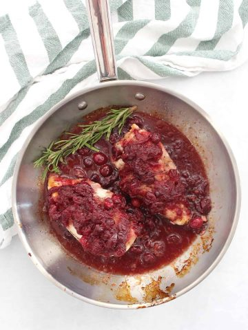 Two cranberry covered chicken breasts in a skillet with sauce and fresh rosemary.