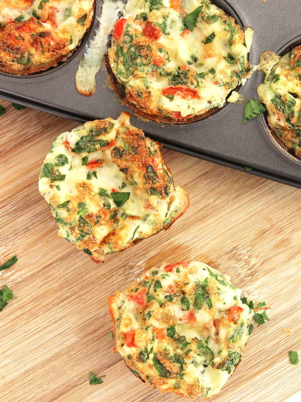 Two egg muffins on a wooden chopping board.