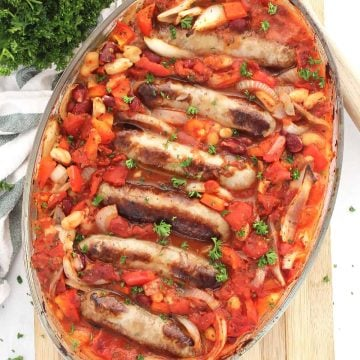 Sausage and bean casserole in a glass baking dish on a wooden chopping board.