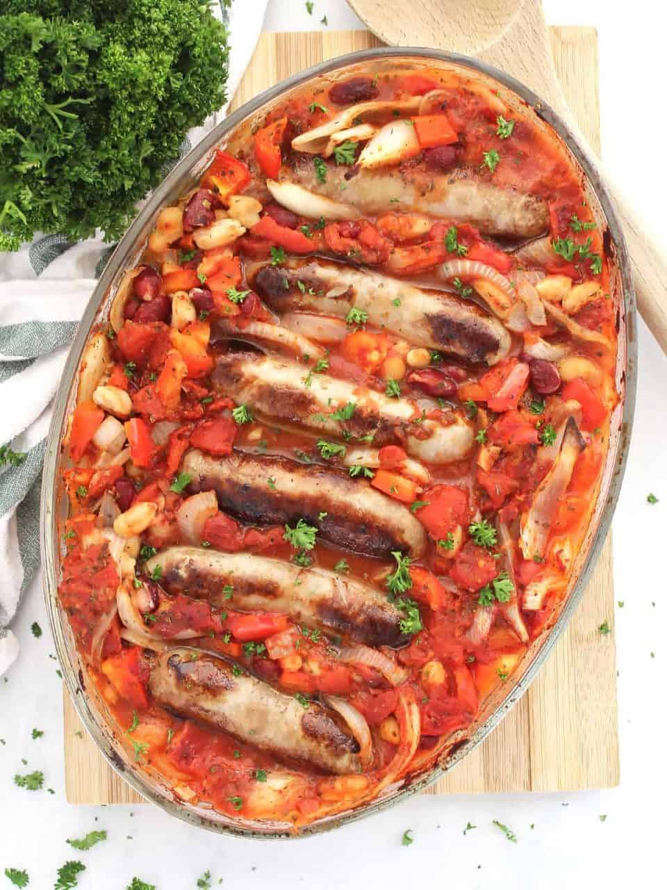Sausage and bean casserole in a baking dish next to a wooden spoon and fresh herbs.
