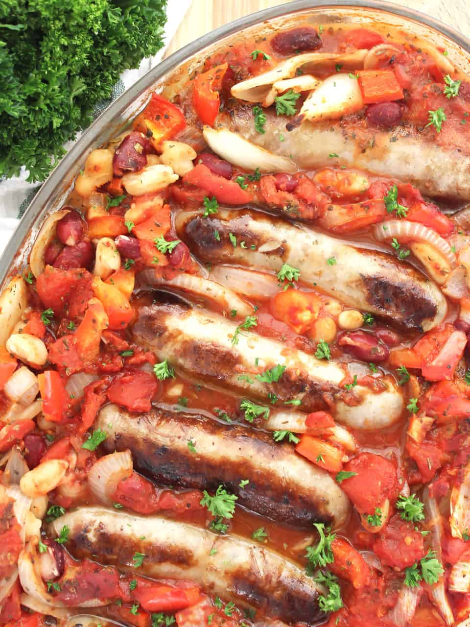 Five sausages in the bean and tomato casserole in a glass baking dish.