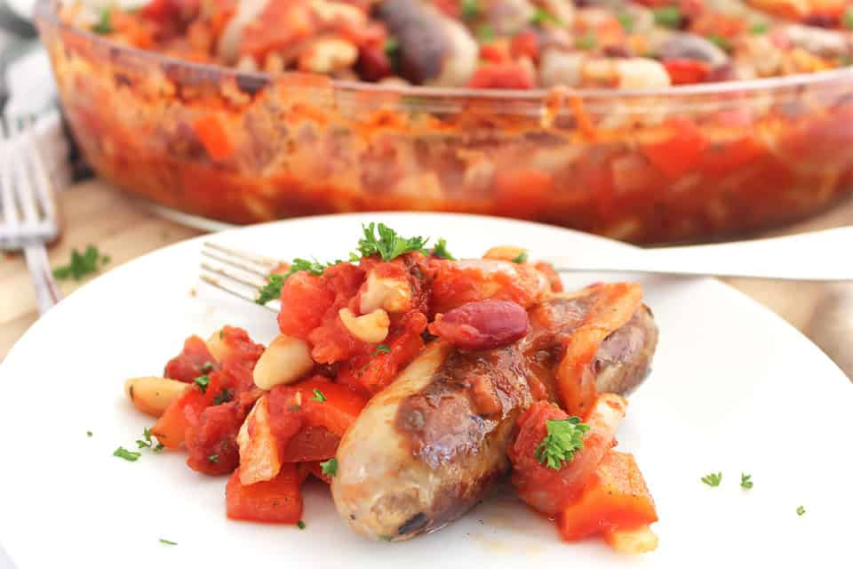 Close up of a serving of sausage and bean casserole on a white plate.