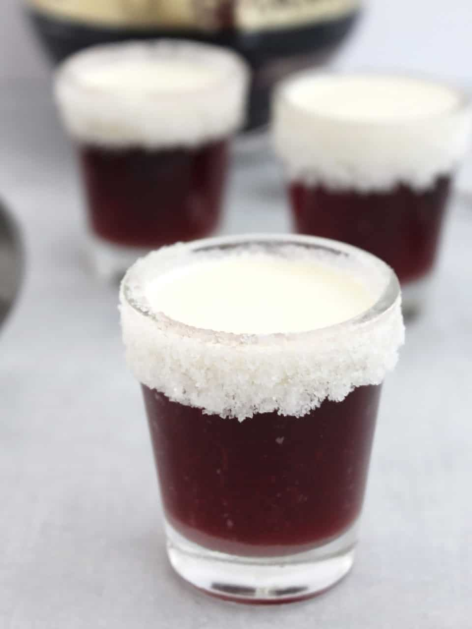 Three chambord shots topped with cream ready to drink.