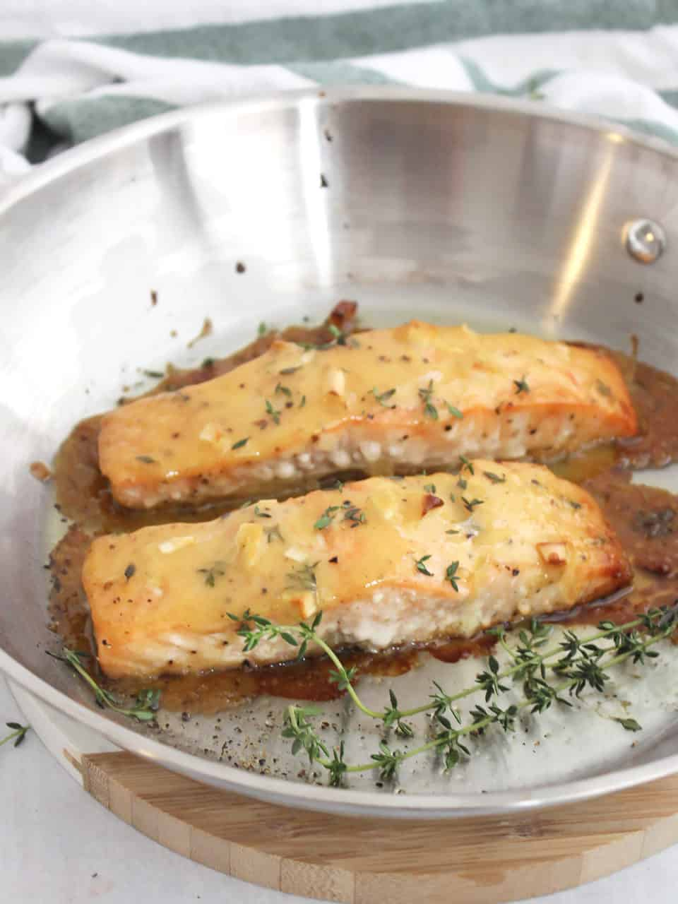 Two cooked salmon fillets in a metal skillet.