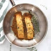 Two salmon fillets in a metal skillet with a honey and mustard sauce.