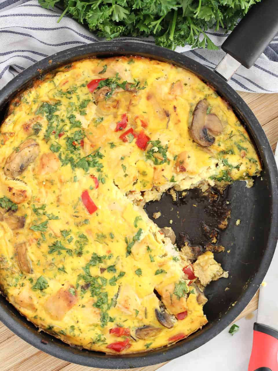 A frittata in a skillet with a slice cut out of it.