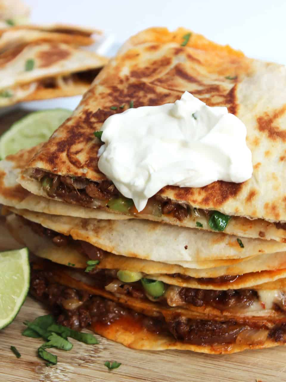 Sour cream served on top of beef and cheese quesadillas.