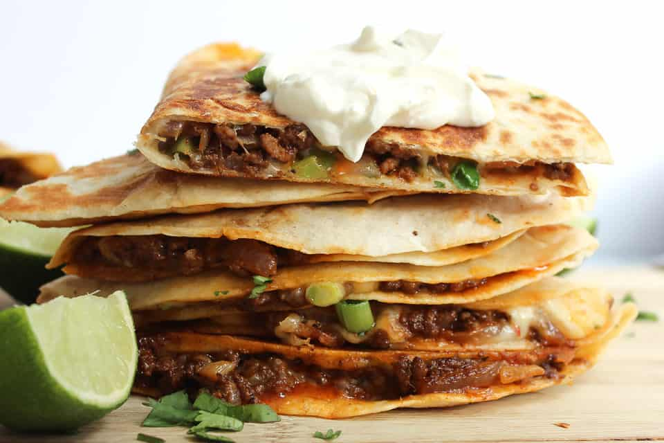 Ground beef quesadillas served with sour cream and lime wedges.
