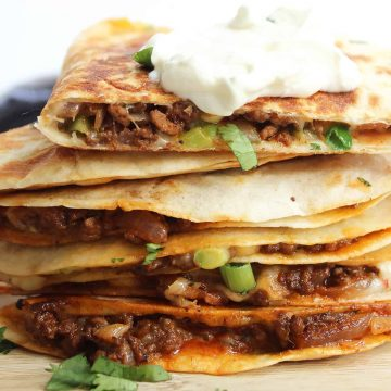 A stack of quesadillas topped with sour cream.