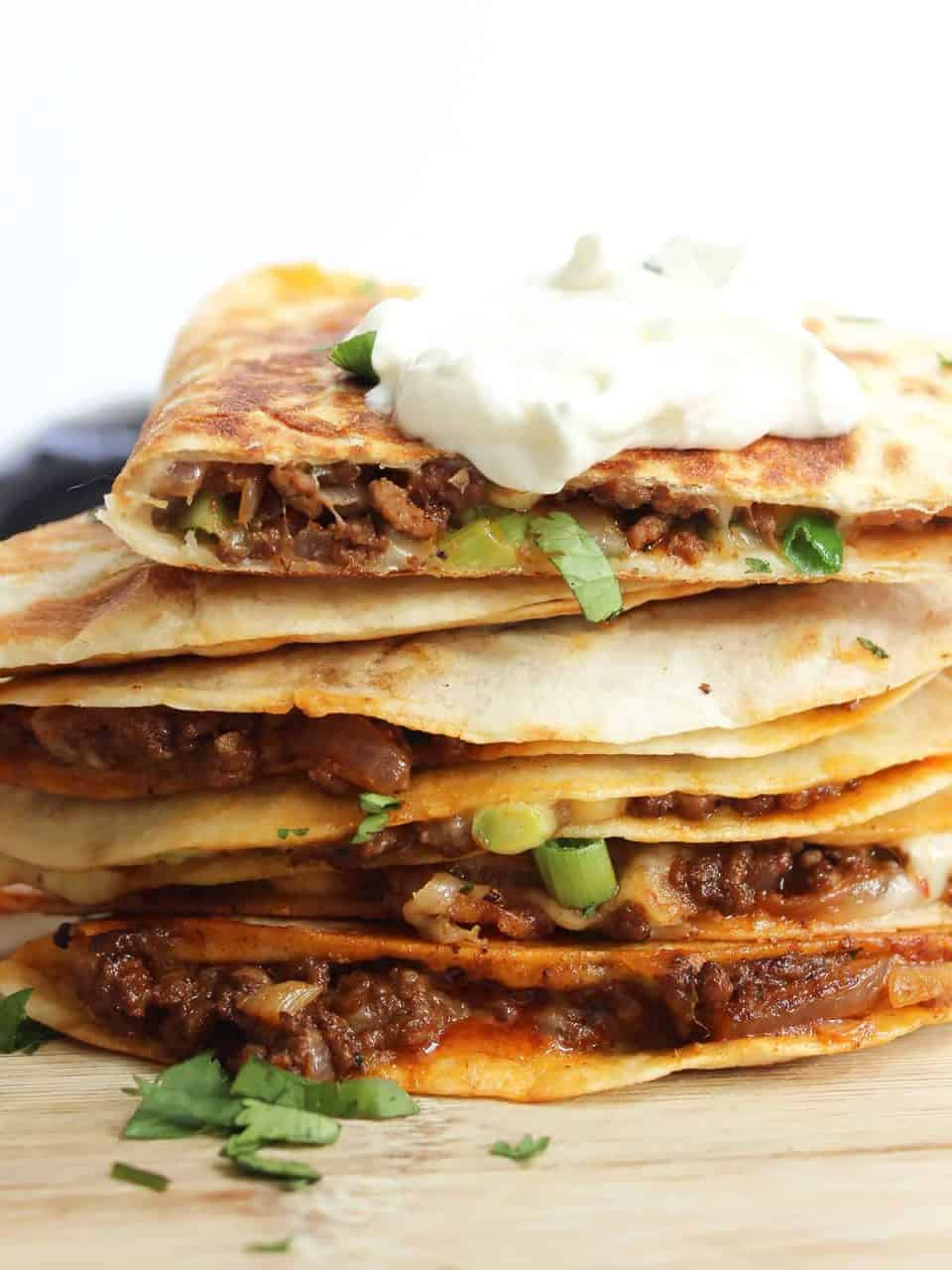 Ground beef quesadillas served with sour cream and fresh cilantro.