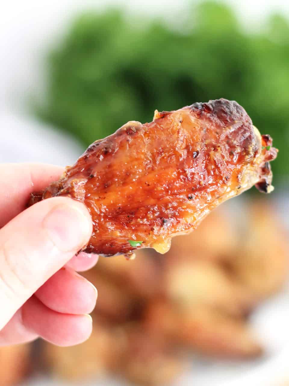 A hand holding a baked chicken wing.