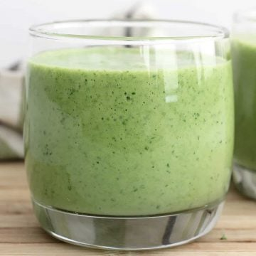 A mango and spinach smoothie in a small glass.