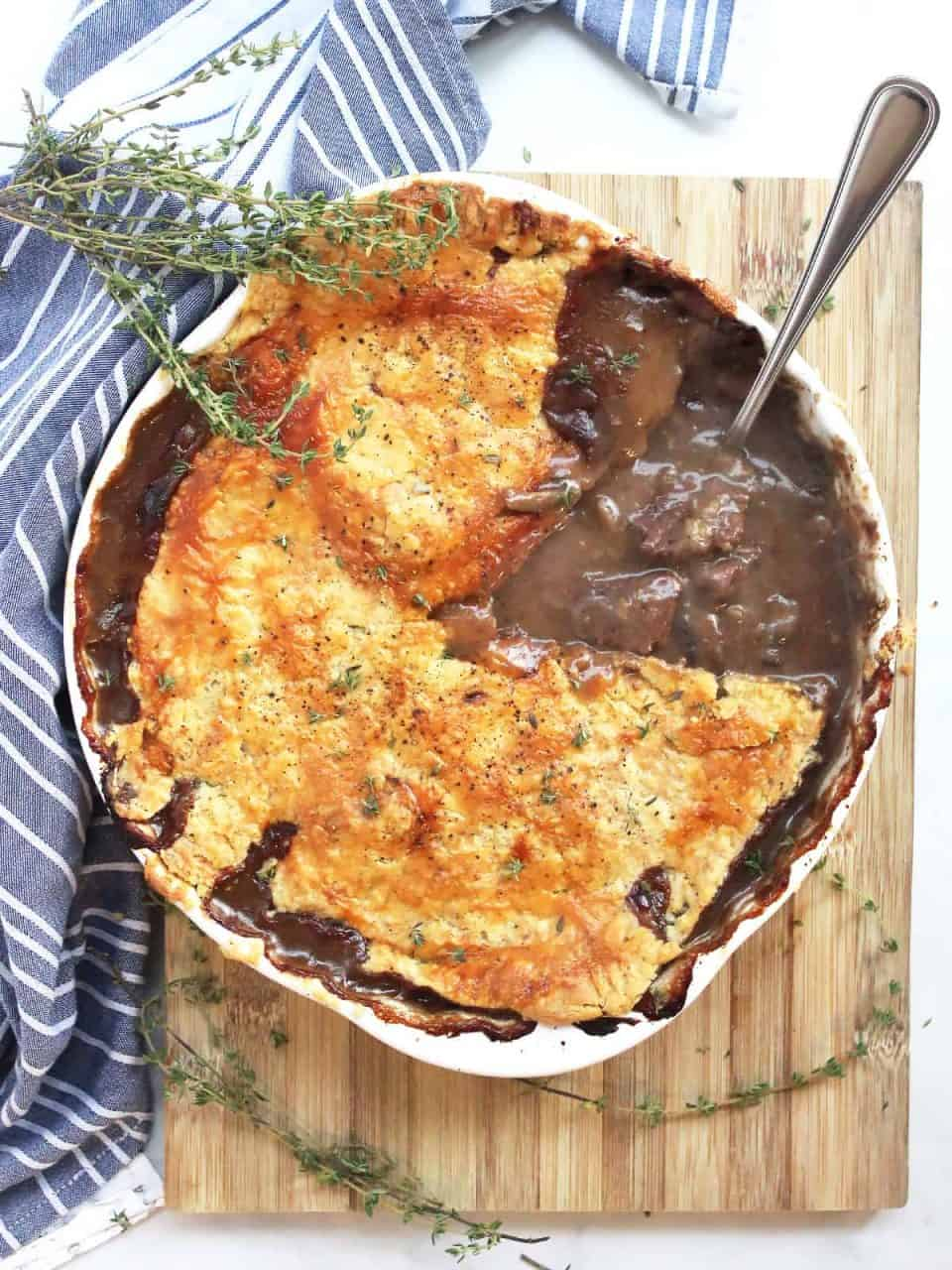 A steak and stilton pie with part of the filling showing. Garnished with fresh thyme.