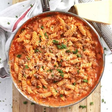 Tomato and goats cheese pasta in a silver skillet.