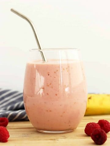 A raspberry banana smoothie in a glass with a straw next to fresh fruits.