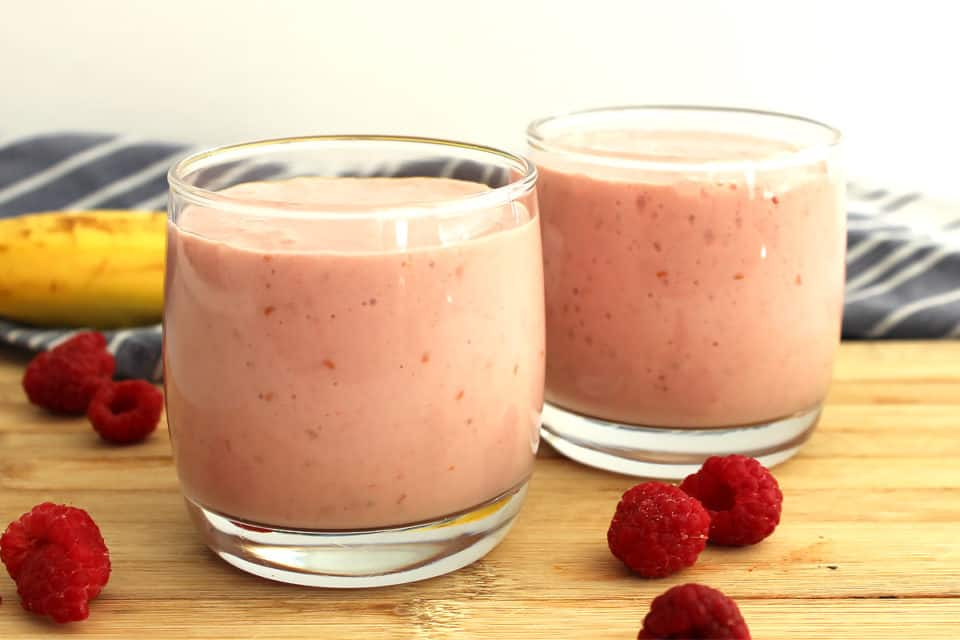 Two small glasses of banana and raspberry smoothie.