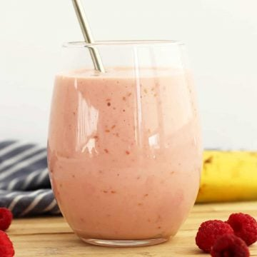 A raspberry banana smoothie in a glass with a straw.