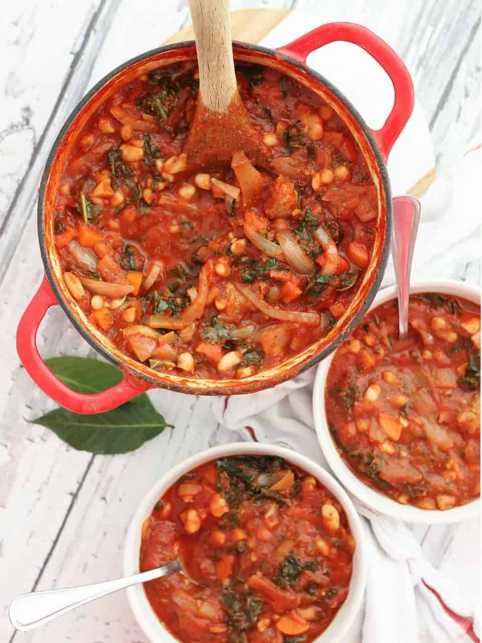 Sausage, kale and bean soup in a dutch oven and served into two white bowls.