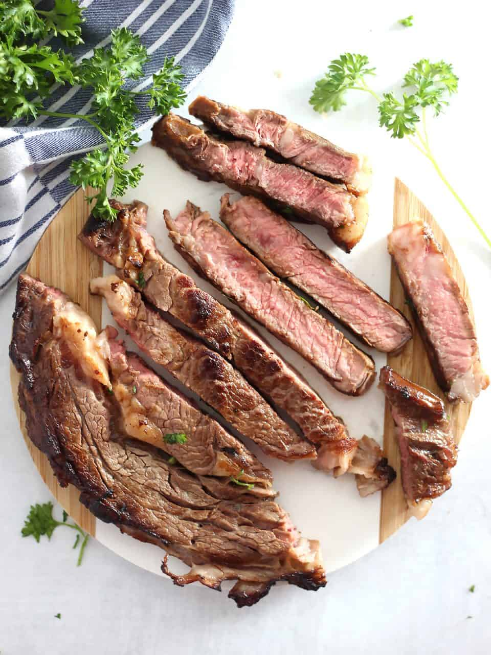 The beer marinated steak sliced into strips on a wooden chopping board.
