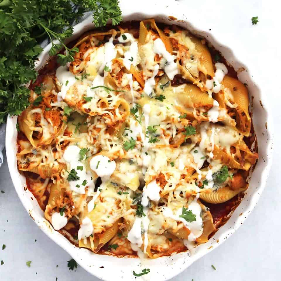 Buffalo chicken stuffed shells in a round baking dish drizzled with ranch dressing.