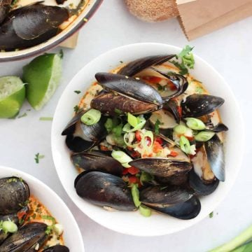 Chili mussels served in a white bowl and garnished with green onions.