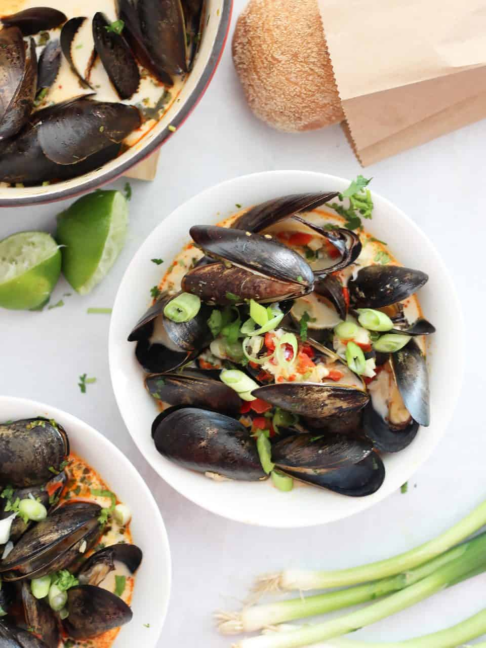 Two bowls of chili mussels next to a fresh lime.