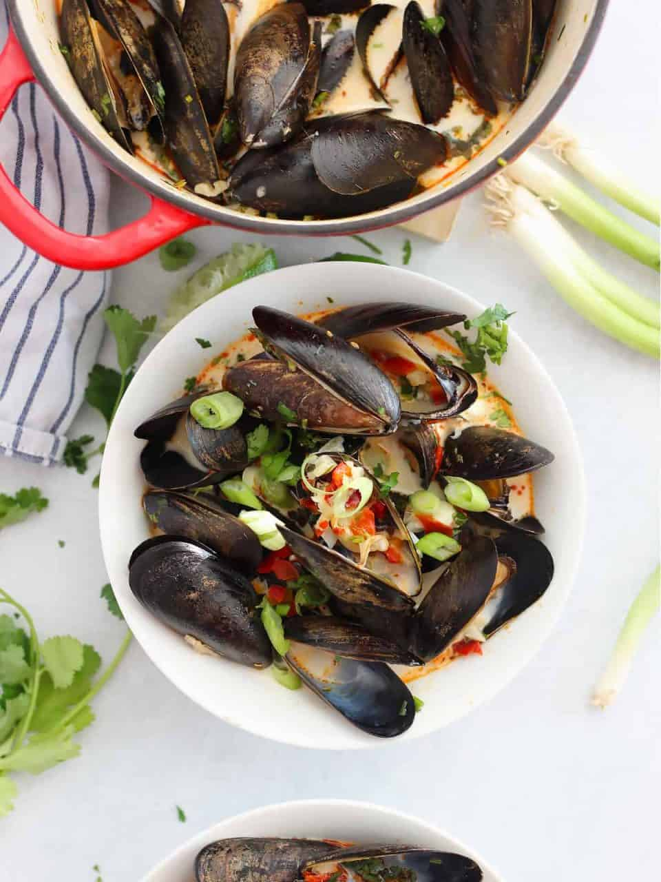 Overhead shot of mussels in a white bowl next to fresh herbs.