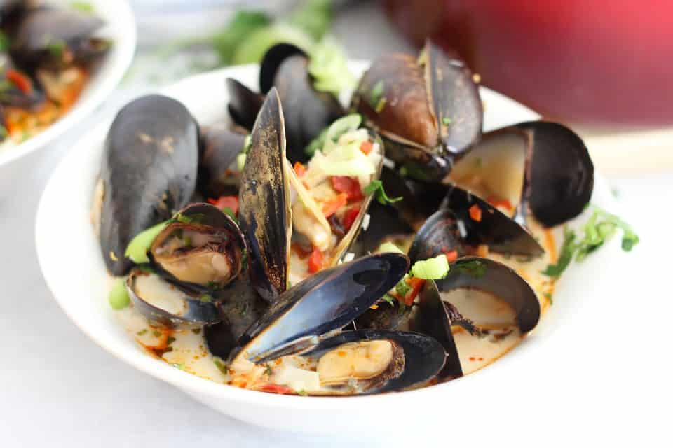 Close up of chili mussels in a white bowl served in coconut milk.
