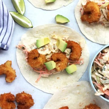Three fried shrimp with slaw and avocado on a small flour tortilla.