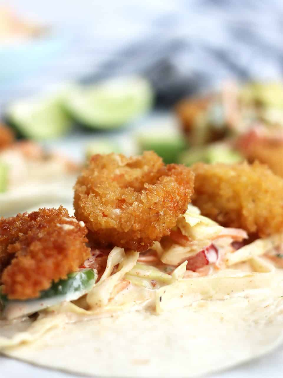 Close up of three breaded shrimp on coleslaw.
