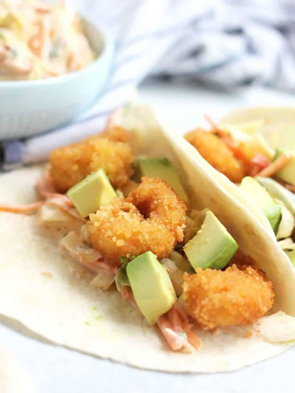 A folded fried shrimp taco with chunks of avocado.