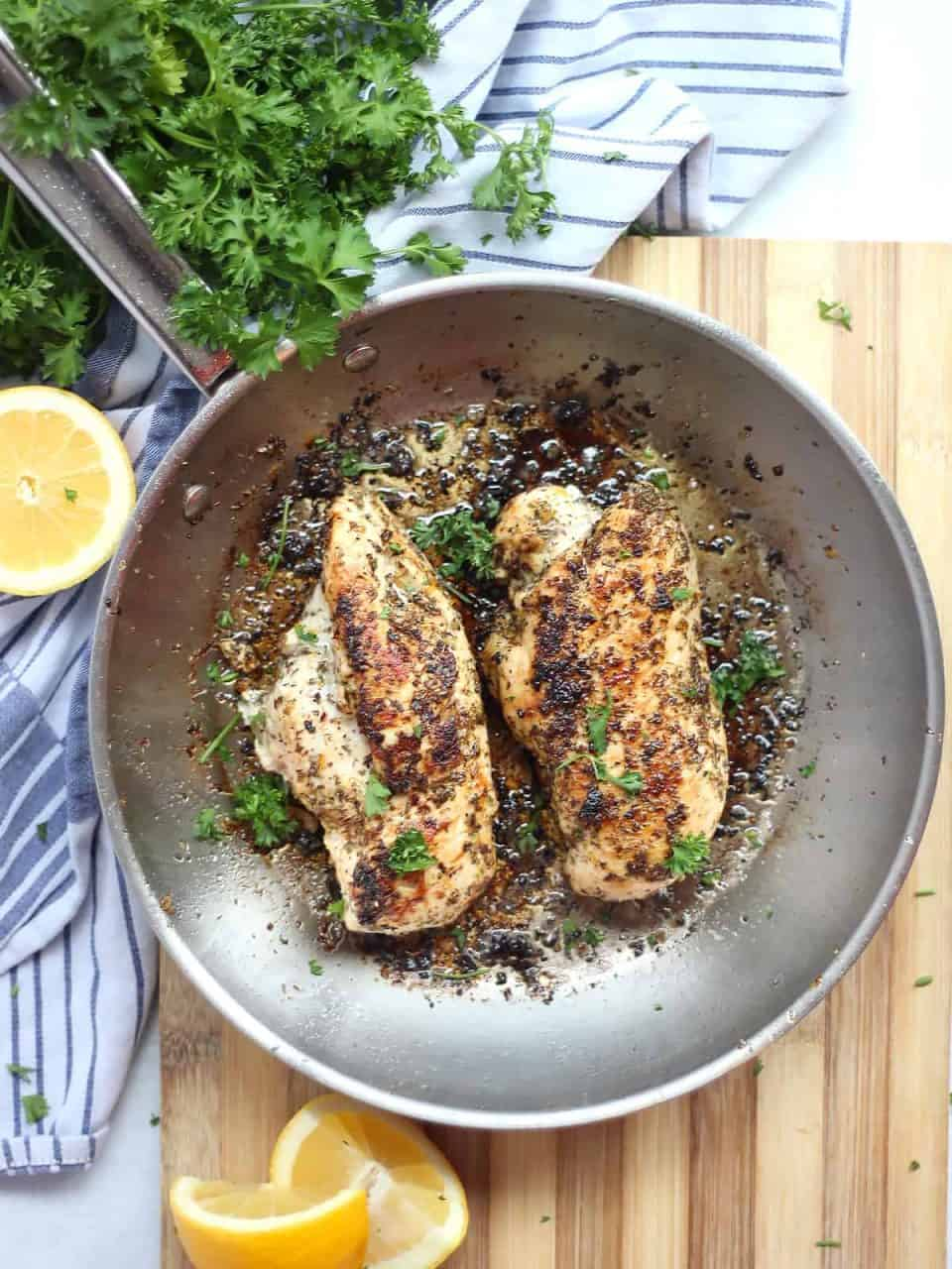 Two lemon oregano chicken breasts in a skillet garnished with fresh parsley.