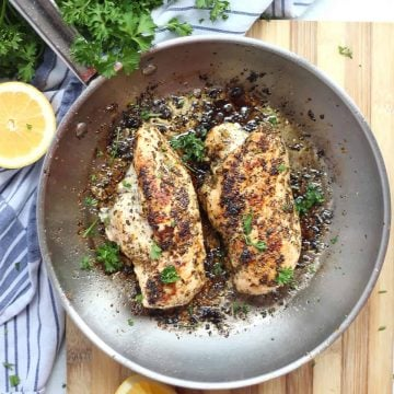 Two lemon oregano chicken breasts cooked in a skillet.